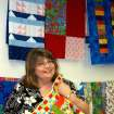 Rose State College's Associate Dean and Professor of Sociology is surrounded by the many quilts students have quilted in the quilting classes on campus.  Many of the quilts have been donated to various charities in the community  Community Photo By:  Steve Reeves  Submitted By:  Donna, Choctaw