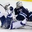Tampa Bay Lightning's Martin St. Louis (26) is smothered by Winnipeg Jets goaltender Ondrej Pavelec (31) during the first period of an NHL hockey game Tuesday, Jan. 7, 2014, in Winnipeg, Manitoba. (AP Photo/The Canadian Press, Trevor Hagan)