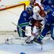 Phoenix Coyotes' Kyle Chipchura centre, kicks the puck into the net past Vancouver Canucks' goalie Roberto Luongo, left, as Daniel Sedin, right, of Sweden, defends during the second period of an NHL hockey game in Vancouver, British Columbia, on Sunday, Jan. 26, 2014. (AP Photo/The Canadian Press, Darryl Dyck)
