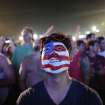 A soccer fan of the U.S. national soccer team watches a live broadcast of the soccer World Cup match between USA and Ghana, inside the FIFA Fan Fest area on Copacabana beach, Rio de Janeiro, Brazil, Monday, June 16, 2014. (AP Photo/Leo Correa)