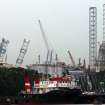 A backup rig, left, is seen tilted to one side off a shipyard on Monday Dec. 3, 2012 in Singapore. The ministry of manpower reported that about 90 workers were sent to hospitals after a jackup rig at a shipyard in Singapore tilted to one side.(AP Photo/Wong Maye-E)