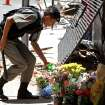 A police officer places flowers outside the Kiss nightclub that were brought by mourners in memory of those who died due to a fire at the club in Santa Maria, Brazil, Monday, Jan. 28, 2013.  A fast-moving fire roared through the crowded, windowless Kiss nightclub in this southern Brazilian city early Sunday, killing more than 230 people. Many of the victims were under 20 years old, including some minors. (AP Photo/Nabor Goulart)