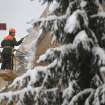 A communal worker cleans a roof after snowfall in the Belarusian capital Minsk, Tuesday, Dec. 11, 2012. The weather forecast predicts continuing snowfall for the next days in Belarus. (AP Photo/Sergei Grits)