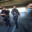SWAT officers search a parking structure during a security check at Los Angeles International Airport on Friday Nov. 1, 2013. A gunman armed with a semi-automatic rifle opened fire at the airport on Friday, killing a Transportation Security Administration employee and wounding two other people. (AP Photo/Ringo H.W. Chiu)