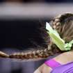 The plait of Belarus' Victoria Azarenka flies as she serves against German Mona Barthel during their quarterfinal match at the Porsche tennis Grand Prix in Stuttgart, Germany, Friday, April 27, 2012. (AP Photo/Michael Probst) ORG XMIT: PSTU113