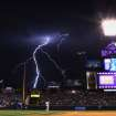 Lightning strikes in the background during the seventh inning of a baseball game between the Colorado Rockies and the San Diego Padres on Monday, July 7, 2014, in Denver. (AP Photo/Jack Dempsey)