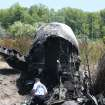 A National Transportation Safety Board official looks through the wreckage at the scene Monday, June 2, 2014, in Bedford, Mass., where a plane plunged down an embankment and erupted in flames during a takeoff attempt at Hanscom Field Saturday night. Lewis Katz, co-owner of the Philadelphia Inquirer and six other people died in the crash. (AP Photo/Boston Herald, Mark Garfinkel, Pool)