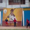 """Two boys stand in front of a fast food advertisement featuring hometown athlete, Detroit Tiger's Miguel Cabrera, during a baseball practice in Maracay, Venezuela, Friday, March 28, 2014. Cabrera's uncle seems unfazed by the news that the Detroit Tigers slugger has netted the richest contract in history of any U.S. sport. Like the rest of the neighborhood, he thinks """"Miguelito,"""" as many in his hometown still call him, was destined for greatness. (AP Photo/Alejandro Cegarra)"""