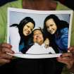 FILE - In this Feb. 15, 2013 file photo, a woman holds a newly purchased copy of  a photo released by the government, showing Venezuela's President Hugo Chavez with two of his daughters, in Caracas,Venezuela. After more than eight years covering Venezuela, AP reporter Ian James finishes his assignment believing Venezuela's many long-term challenges, such as crime, corruption, a troubled economy and bitter political divisions, can seem as vast as the sea of crude oil that Venezuela sits atop. And with Chavez battling cancer, the country could be headed for big political shifts and possible turmoil. But James takes the view that the country's problems can be solved. (AP Photo/Fernando Llano, File)