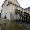 Charoene Taylor walks through flood water outside her home in the Bowleys Quarters section of Baltimore County, Md. as the aftermath of superstorm Sandy continued to disrupt routines on the East Coast Tuesday, Oct. 30, 2012. Sandy, the storm that made landfall Monday, caused multiple fatalities, halted mass transit and cut power to more than 6 million homes and businesses. (AP Photo/Steve Ruark) ORG XMIT: MDSR109