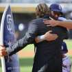 San Diego Padres' Hall of Fame pitcher Trevor Hoffman, left, hugs Padres' Mark Kotsay, right, after he presented a custom surfboard to Kotsay before a baseball game against the Arizona Diamondbacks on Thursday, Sept. 26, 2013, in San Diego. (AP Photo/Don Boomer)
