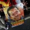 A supporter of Venezuela's President  Hugo Chavez holds poster of him with the slogan in Spanish
