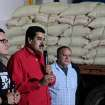 In this photo provided by Miraflores Presidential Press Office, Venezuela's Vice President Nicolas Maduro, center, delivers a speech during a visit to