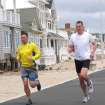 Joggers run past a house damaged by Superstorm Sandy on the Manasquan, N.J., beachfront, Saturday, May 25, 2013. Communities that were hard-hit by Superstorm Sandy, including Manasquan, are hoping for a profitable summer season to help them recover. (AP Photo/Wayne Parry)