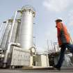 FILE - In this April 8, 2013, file photo, an employee of energy company Eon Hanse walks across the premises of the natural gas storage facility in Hamburg-Reitbrook, Germany. Clean Energy refers to energy that pollutes less than coal and oil, the dominant sources of fuel for electricity and transportation. Natural gas is considered by some, including the Obama administration, to be clean because it emits far fewer pollutants than coal or oil. Others consider only renewable energy truly clean. (AP Photo/dpa, Bodo Marks)