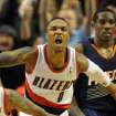 Portland Trail Blazers point guard Damian Lillard (0) celebrates as Phoenix Suns point guard Eric Bledsoe (2) looks on as time runs out in the NBA basketball game on Wednesday, Nov. 13, 2013, in Portland, Ore. The Blazers won the game 90-89. (AP Photo/Steve Dykes)