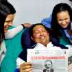 In this photo released Friday, Feb. 15, 2013 by Miraflores Presidential Press Office, Venezuela's President Hugo Chavez, center, poses for a photo with his daughters, Maria Gabriela, left, and Rosa Virginia as he holds a copy of Cuba's state newspaper Granma at an unknown location in Havana, Cuba, Thursday, Feb. 14, 2013. Chavez remains in Havana undergoing unspecified treatments following his fourth cancer-related operation on Dec. 11. He has hasn't been seen or spoken publicly in more than two months. (AP Photo/Miraflores Presidential Press Office)