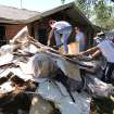 Texas A&M  students clean debris at a home in West, Texas, Saturday, May 4, 2013, that was damaged due to the explosion at a fertilizer plant in West on April 17. The plant that exploded, killing 14 people, injuring more than 200 others and causing tens of millions of dollars in damage to the surrounding area, had only $1 million in liability coverage, lawyers said Saturday. (AP Photo/Waco Tribune Herald, Rod Aydelotte)