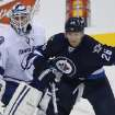Tampa Bay Lightning goaltender Anders Lindback (39) and Winnipeg Jets' Blake Wheeler (26) watch a flying puck during the first period of an NHL hockey game Tuesday, Jan. 7, 2014, in Winnipeg, Manitoba. (AP Photo/The Canadian Press, Trevor Hagan)