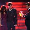 Finalists Jessica Sanchez, left, and Phillip Phillips, center, listen as host Ryan Seacrest announces the winner onstage at the
