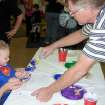 Charlie Stowe helps a Family Fall Festival participant get ready to do handprints at the Arts and Crafts booth at the Family Fall Festival and Trunk or Treat event at First Christian Church in Guthrie on Sunday, Oct. 28.  Community Photo By:  Karen Allen  Submitted By:  Karen,