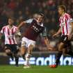 West Ham United's Andy Carroll, left, vies for the ball with Sunderland's captain Wes Brown, right, during their English Premier League soccer match at the Stadium of Light, Sunderland, England, Monday, March 31, 2014. (AP Photo/Scott Heppell)