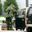 A member of the Oklahoma City Police Department bomb squad removes a suspicious package from a trash can outside City Hall in Oklahoma City, Oklahoma April 28, 2009.  Photo by Steve Gooch, The Oklahoman
