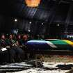 South African President Jacob Zuma, seated next to Winnie Madikizela-Mandela, right, Nelson Mandela's former wife, and Nelson MandelaÂ's widow Graca Machel attend the funeral service for former South African President Nelson Mandela in Qunu, South Africa, Sunday, Dec. 15, 2013. (AP Photo/Felix Dlangamandla, Pool)