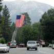 A ladder truck flies the American flag to greet residents back to Idyllwild after the evacuation order was rescinded Sunday, July 21, 2013, in the areas affected by the Mountain Fire. Thousands of people were allowed to return to their homes in Southern California mountain communities near Palm Springs on Sunday, after firefighters aided by heavy rain made substantial progress against a week-old wildfire that has burned across 42 square miles and destroyed seven homes. (AP Photo/The Press-Enterprise, Terry Pierson)