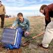 Graduate student Gabriel Mattei digs beneath a box held up by Katie Keranen, an assistant professor at the OU School of Geology and Geophysics,  as the two place a seismometer and this recording device into the ground on the property of Joseph and Mary Reneau Saturday afternoon, Nov. 5. , 2011.  The pair are accompanied by Austin Holland, left, a research seismologist with the Oklahoma Geological Survey.  They are placing the devices on the Reneau property after an earthquake rattled the area in the area in the early morning hours Saturday.  The Reneaus  were awakened around 2:15 a.m. when their house shook and items began falling off the walls and form shelves and cabinets inside their two-story brick ranch-style  home in rural Lincoln County, about  six miles northwest of Prague. Holland placed the quake's epicenter within two to three miles of the Reneau home.   Photo by Jim Beckel, The Oklahoman  ORG XMIT: KOD