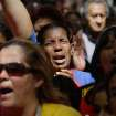 Women react as they gather at Simon Bolivar square in support of Venezuela's President Hugo Chavez in Caracas, Venezuela, Sunday Dec.  9, 2012.  Chavez is to return to Cuba Sunday for another surgery in his battle against cancer, which has led him to speak publicly of a successor for the first time.  Chavez said Saturday that if there are