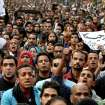 Egyptians attend the funeral of Gaber Salah, also known as 'Jika,' who was who was killed in clashes with security forces during his funeral procession in Cairo, Egypt, Monday, Nov. 26, 2012. Thousands of Egyptians on Monday gathered into Cairo's Tahrir Square to attend the funeral of Salah, who was severely injured during clashes with security forces last week and died Sunday night. The poster at right in Arabic reads,