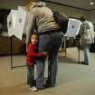 Alexis Svetlick, 2, of Moline Ill., sticks close to her mother, Jennifer Svetlick, while she votes at First Christian Church in Moline, Ill. on Tuesday Nov. 6, 2012. Morning rain did not deter voters from heading to the polls, with long lines reported at numerous polling places. (AP Photo/The Dispatch, Todd Mizener) QUAD CITY TIMES OUT