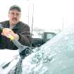 Stan Wojciechowski of Jonesboro scrapes ice from his windshield Friday in the parking lot of Kroger in Jonesboro.