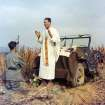 In this photo provided by Col. Raymond A. Skeehan, Father Emil Kapaun celebrates Mass using the hood of his jeep as an altar, as his assistant, Patrick J. Schuler, kneels in prayer in Korea on Oct. 7, 1950, less than a month before Kapaun was taken prisoner. Kapaun died in a prisoner of war camp on May 23, 1951, his body wracked by pneumonia and dysentery. On April 11, 2013, President Barack Obama will award the legendary chaplain, credited with saving hundreds of soldiers during the Korean War, the Medal of Honor posthumously. (AP Photo/Col. Raymond A. Skeehan via The Wichita Eagle)