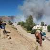 CORRECTS DATE TO TUESDAY, MAY 22, 2012 - Firefighters battle a wind-driven fire that has destroyed at least two homes and a number of outbuildings in Topaz Ranch Estates, south of Gardnerville, Nev., on Tuesday, May 22, 2012. (AP Photo/Cathleen Allison)