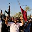 In this Tuesday, June 17, 2014 photo, Iraqi Shiite tribal fighters raise their weapons and chant slogans against the al-Qaida-inspired Islamic State of Iraq and the Levant, after authorities urged Iraqis to help battle insurgents, in Baghdad's Sadr city, Iraq. Thousands of Shiites from Baghdad and across southern Iraq answered an urgent call to arms Saturday, joining security forces to fight the Islamic militants who have captured large swaths of territory north of the capital and now imperil a city with a much-revered religious shrine. (AP Photo/Karim Kadim)
