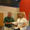 Helen Hubble, human resources manager for SITEL, (right) presents a check for $700 to Uwe von Schamann, director of development for the J. D. McCarty Center, on behalf of the 400 SITEL employees in Norman. Each quarter the SITEL employees select a non-profit organization to support through fundraising activities within the company. This donation will go to the McCarty Center's Camp ClapHans summer camp scholarship fund.  Community Photo By:  Greg Gaston  Submitted By:  Greg,