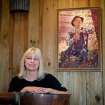 "In this Friday, Nov. 16, 2012 photo, entrepreneur Cheryl ""Happy"" Wood stands under a portrait of her grandfather Simmie Free in the Dawsonville Moonshine Distillery, in Dawsonville, Ga. Distillers are making their first batches of legal liquor in this tiny Georgia town's hall, not far from the mountains and the maroon, orange and gold canopy of trees that once hid bootleggers from the law. (AP Photo/David Goldman)"