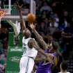 Sacramento Kings center DeMarcus Cousins, center, drives to the basket against the defense of Boston Celtics center Joel Anthony (50) during the first half of an NBA basketball game on Friday, Feb. 7, 2014, in Boston. (AP Photo/Mary Schwalm)