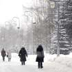 People walk in the park as snow falls in the Belarus capital Minsk, Tuesday, March 12, 2013.  Winter weather with frost and snow continues to prevail in Belarus. (AP Photo/Sergei Grits)