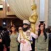 Sacha Baron Cohen, center, smiles after dropping a substance on the red carpet as he arrives before the 84th Academy Awards on Sunday, Feb. 26, 2012, in the Hollywood section of Los Angeles. (AP Photo/Chris Pizzello) ORG XMIT: OSC259