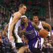 Utah Jazz's Andris Biedrins, left, defends as Sacramento Kings' Isaiah Thomas (22) drives the basket in the first half of an NBA basketball game on Saturday, Dec. 7, 2013, in Salt Lake City. (AP Photo/Kim Raff)