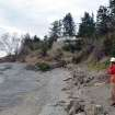 This March 27, 2013 photo provided by the Washington Dept. of Natural Resources, DNR geologist Stephen Slaughter surveys a damaged home near the bottom of a massive landslide that also isolated or threatened more than 30 others near Coupeville, Wash.  Geologists and engineers are assessing what might happen next after a large landside thundered down the scenic island hillside overlooking Puget Sound.  (AP Photo/Washington Dept. of Natural Resources)
