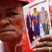 A supporter of Venezuela's President Hugo Chavez holds a photo of him, alongside Cuba's Raul Castro, right, and Fidel Castro, during a event to commemorate the violent street protests of 1989 known as the