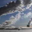 Men walk in snow covered field as smoke from a heating plant is seen on a winter's morning in Minsk, Belarus, Wednesday, Jan. 23, 2013. Temperatures of minus 14 degree Celsius (minus 6.8 degree Fahrenheit) hit the Belarusian capital. (AP Photo/Sergei Grits)