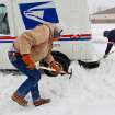 Russell Henderson noticed postal worker George Staros needed some help getting out of a snow drift on Douglas Blvd. near SE 15th Street. Henderson attached a chain from his truck to the mail truck and then helped dig snow from beneath the tires of Staros' vehicle. Within ten minutes, the two men had freed the vehicle and Staros continued with his mail delivery. A winter storm created whiteout conditions and caused snow drifts that made problems for the few motorists who ventured out Tuesday morning, Feb. 1, 2011.    Photo by Jim Beckel, The Oklahoman