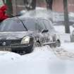 A Belarus man clears snow from his car after heavy snowfall in the capital Minsk, Belarus, Thursday, Jan. 17, 2013.  The snow fell over night and is causing transport problems across the area. (AP Photo/Sergei Grits)