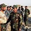 In this Friday, July 4, 2014 photo, Iraqi lawmaker Hakim al-Zamili, center, visits fighters of