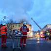 Rescuers stand near a house in Backnang,  Germany Sunday March 10, 2013.  An early-morning fire on Sunday at the apartment building in southwestern Germany left seven people dead, six of them children, police said.  Authorities were alerted to the blaze in Backnang, a town near Stuttgart, at 4.30 a.m. Police said in a statement that they believe the fire broke out in a second-floor apartment, and said that their investigation is focusing on a heater in the apartment. (AP Photo/dpa, Benjamin Beytekin)